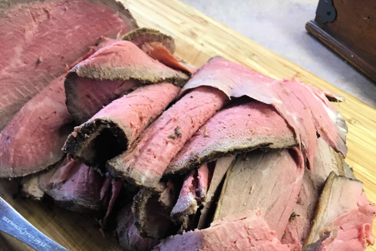 Medium rare slices of eye of round roast, in a stack.