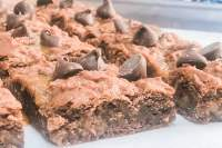 Side shot of Caramel Fat Boy Brownies topped with lots of chocolate chips.