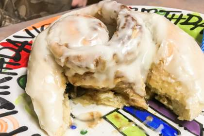 A very large glazed cinnamon roll, partially eaten.