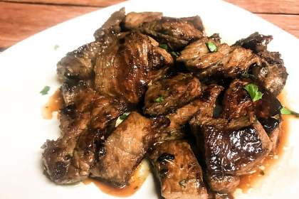 A white plate loaded with marinated steak bites in juices.