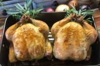 Two oven-roasted chickens side-by-side in a pan.
