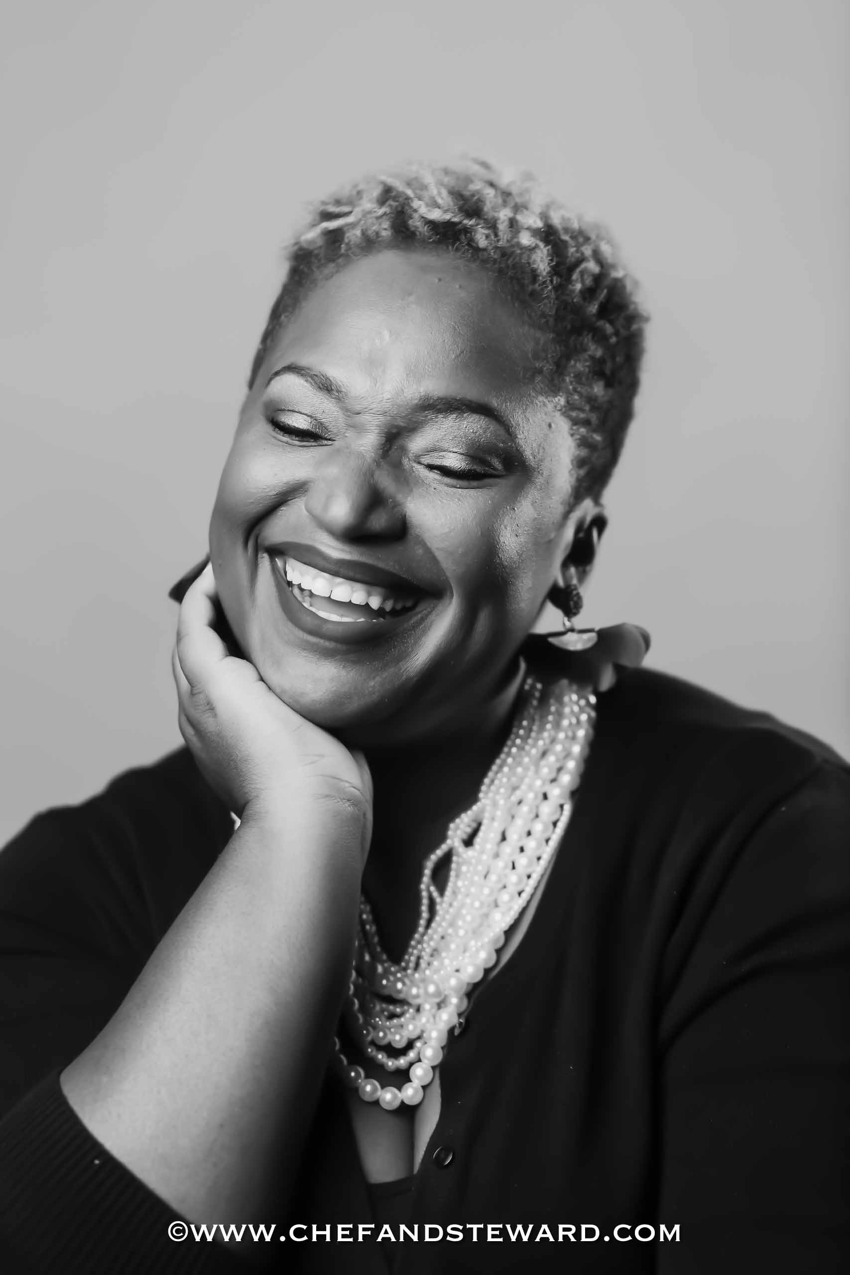 Black and White Portrait of Black woman with pearls laughing black food bloggers and black women who blog