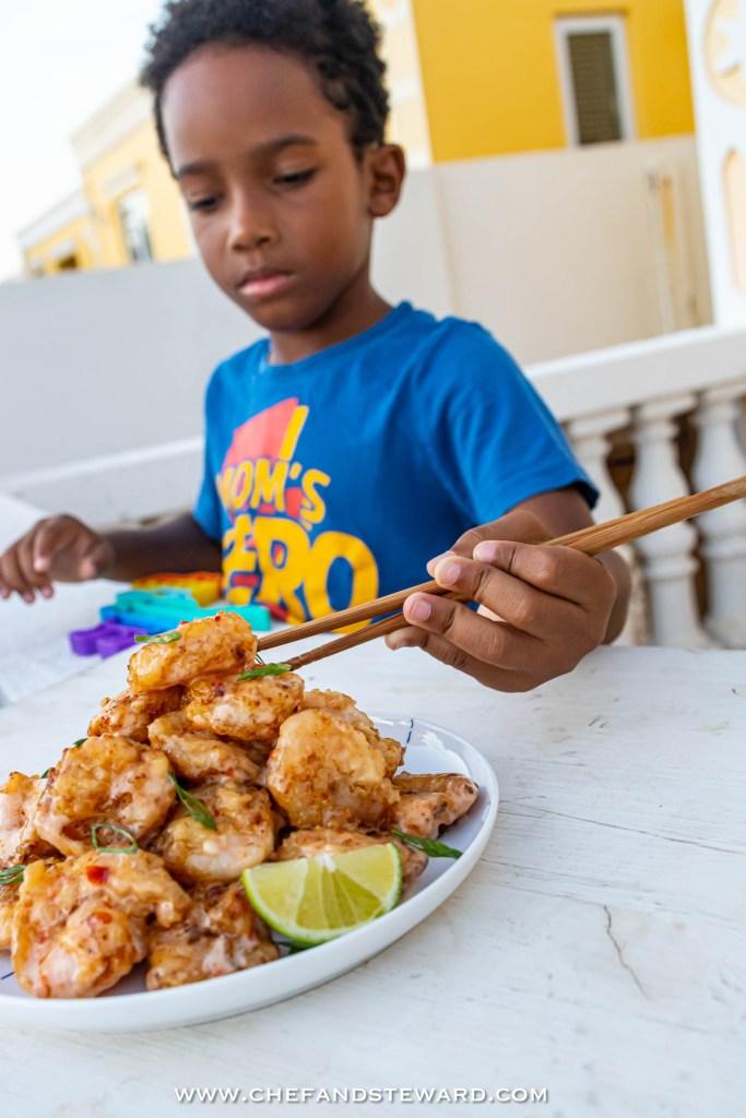 Black boy in bright blue shirt that says mom's hero eating bang bang shrimp or rock shrimp tempura with chopsticks