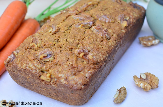 Close up picture of freshly baked carrot cake with fresh carrots beside it on a table