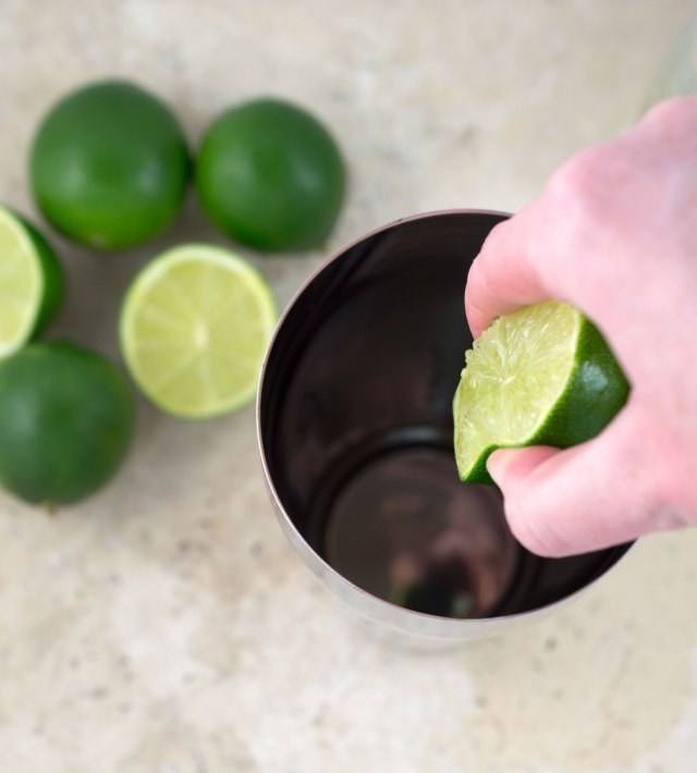 Top shot of lime juice being squeed from wedge into cocktail shaker.