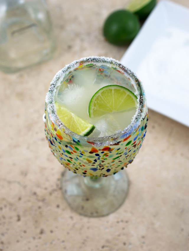 Top shot of classic margarita with lime wedges inside glass.