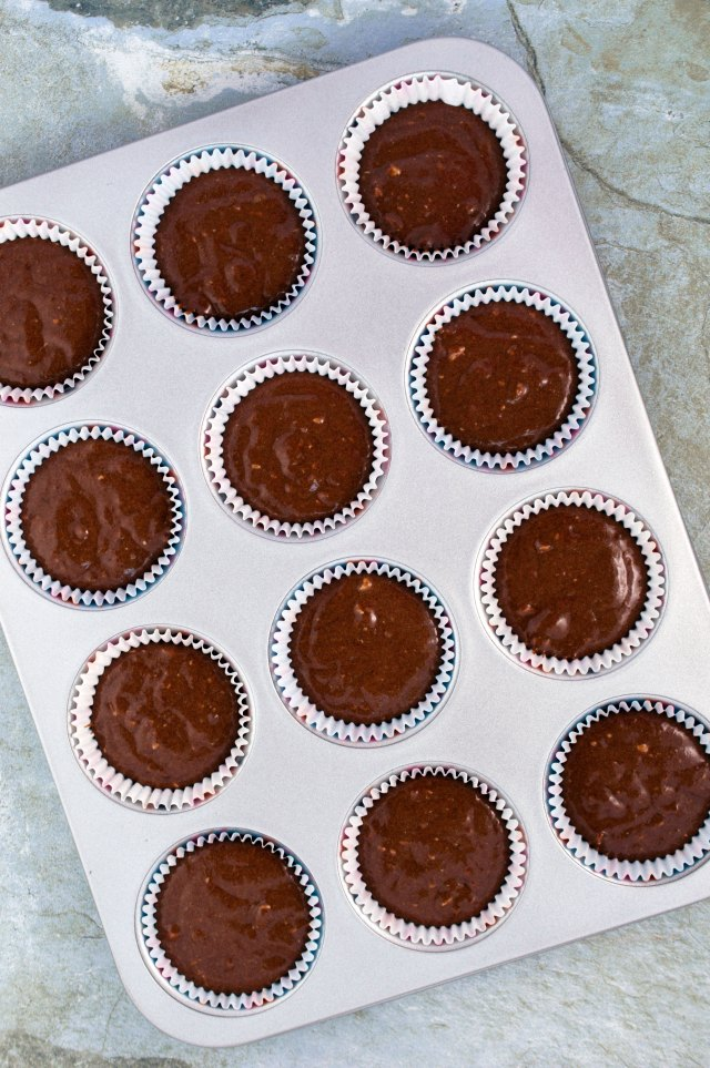 raw chocolate cake dough divided into cupcake molds in a metal cupcake tin   chefsavvy.com