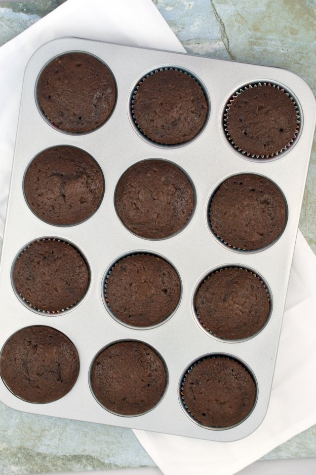 cooked chocolate cake dough divided into cupcake molds in a metal cupcake tin   chefsavvy.com