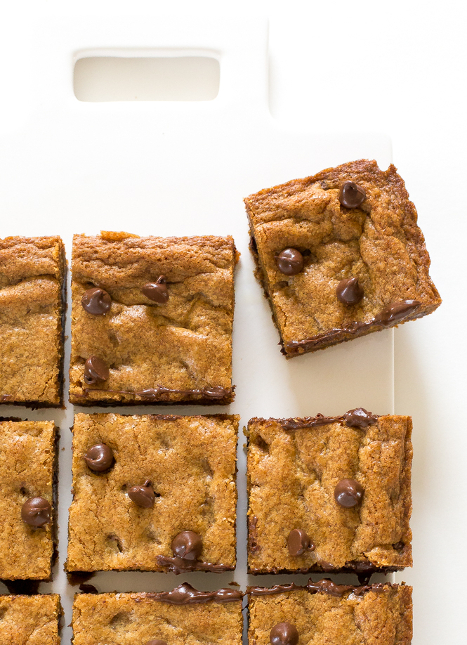 top shot of Browned Butter Chocolate Chip Blondies cut into square on white cutting board