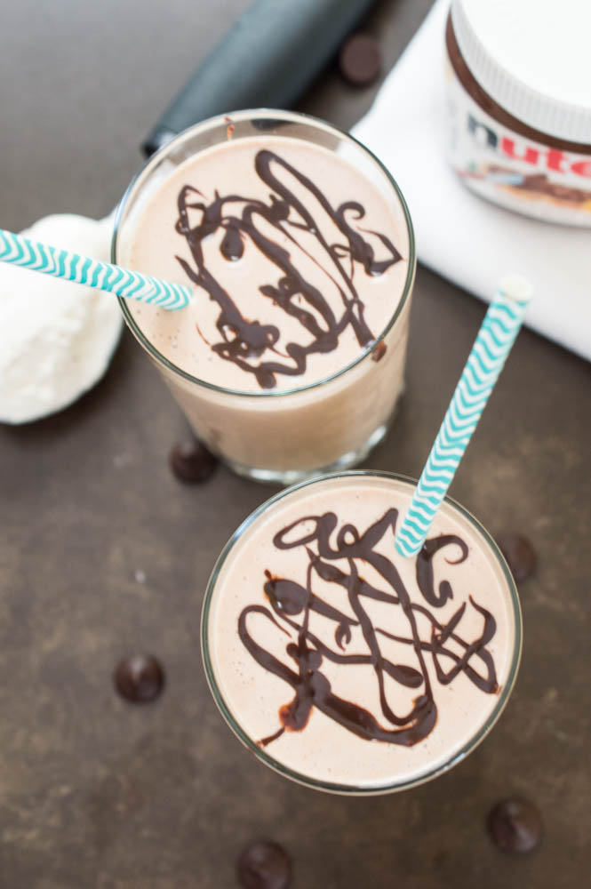 overhead shot, 2 Peanut Butter and Nutella Milkshakes with chocolate swirled on top and blue chevron paper straws. Jar of nutella in background.