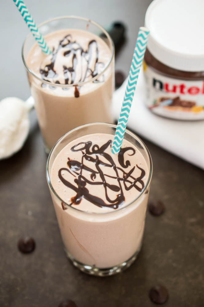 2 Peanut Butter Milkshakes with chocolate swirled on top and blue chevron paper straws. Jar of nutella in background.