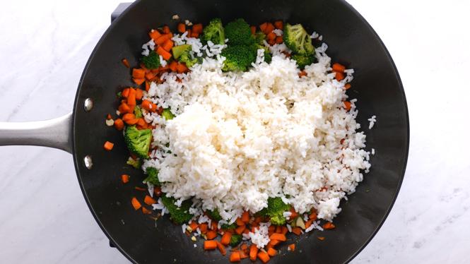 Adding white rice to veggies in black wok