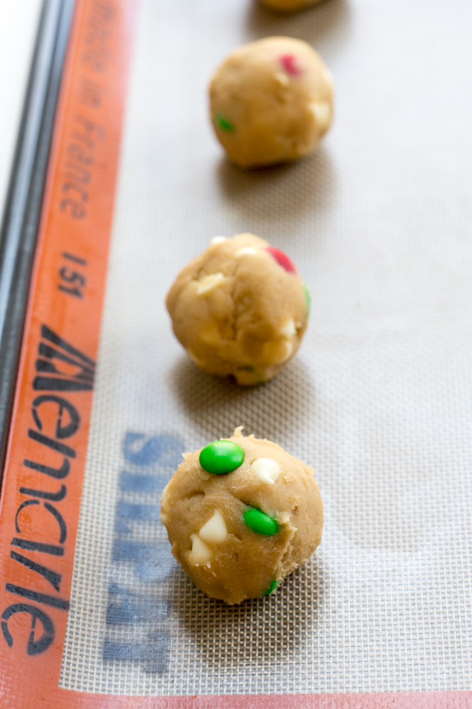 cookie dough rolls on baking pan with red and green m&ms
