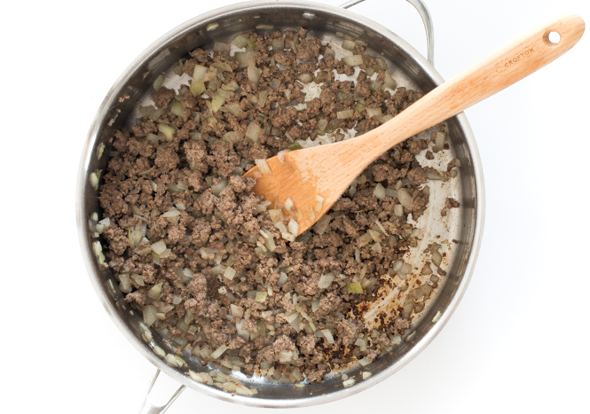 Top shot of ground beef and diced onions cooking in skillet with wooden spoon.