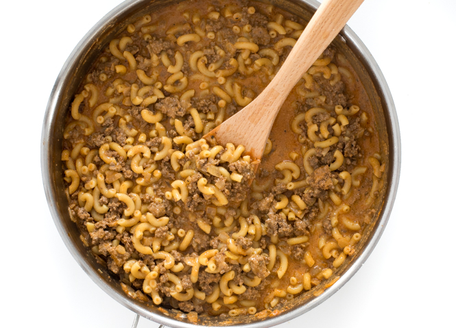 Top shot of macaroni noodles and ground beef cooking in skillet with wooden spoon.