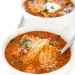 top shot of lasagna noodles in red broth served in two white bowls with spoons