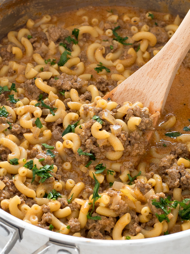 Cooked beef and macaroni pasta in skillet with wooden spoon.