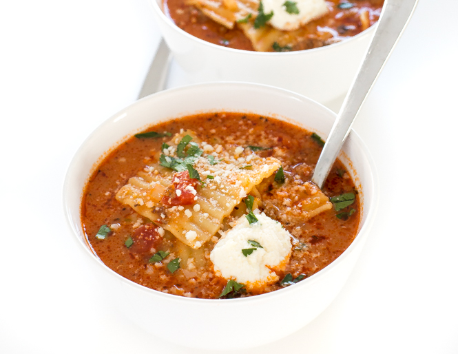 top shot of lasagna soup in white bowl with spoon