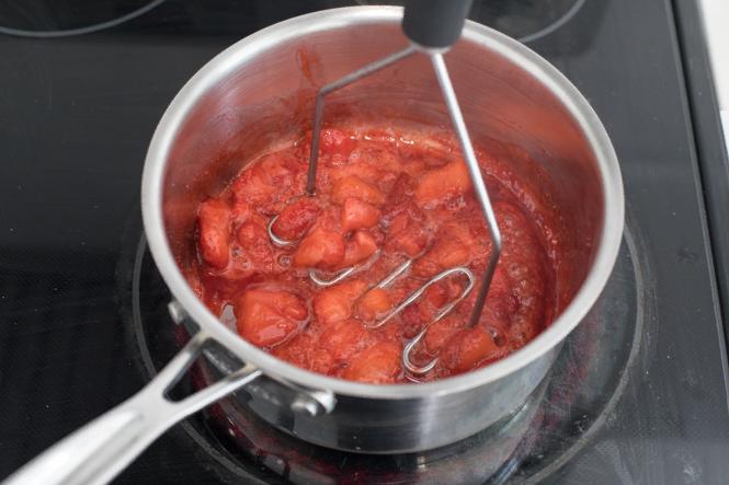Mashing strawberries for strawberry sauce