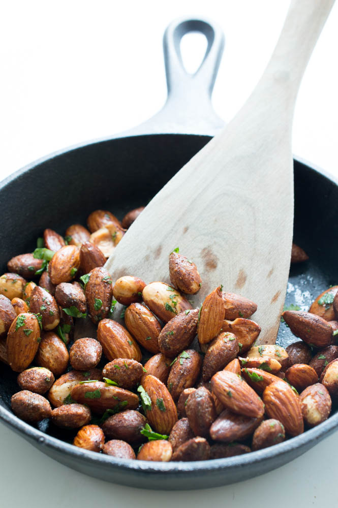 wooden kitchen spoon stirring roasted nuts in black skillet with cilantro flakes