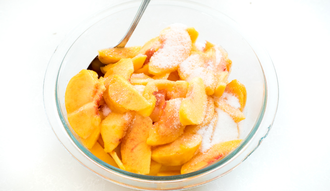 Peaches and sugar in bowl