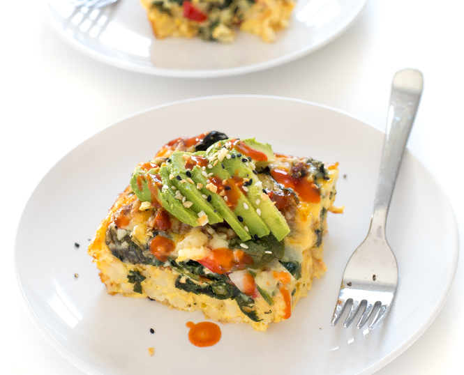 slice of breakfast casserole topped with sliced avocado on white plate