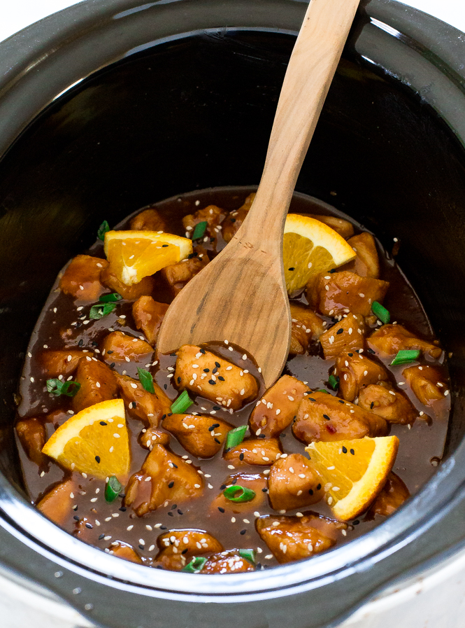 Orange Chicken in a slow cooker with wooden spoon