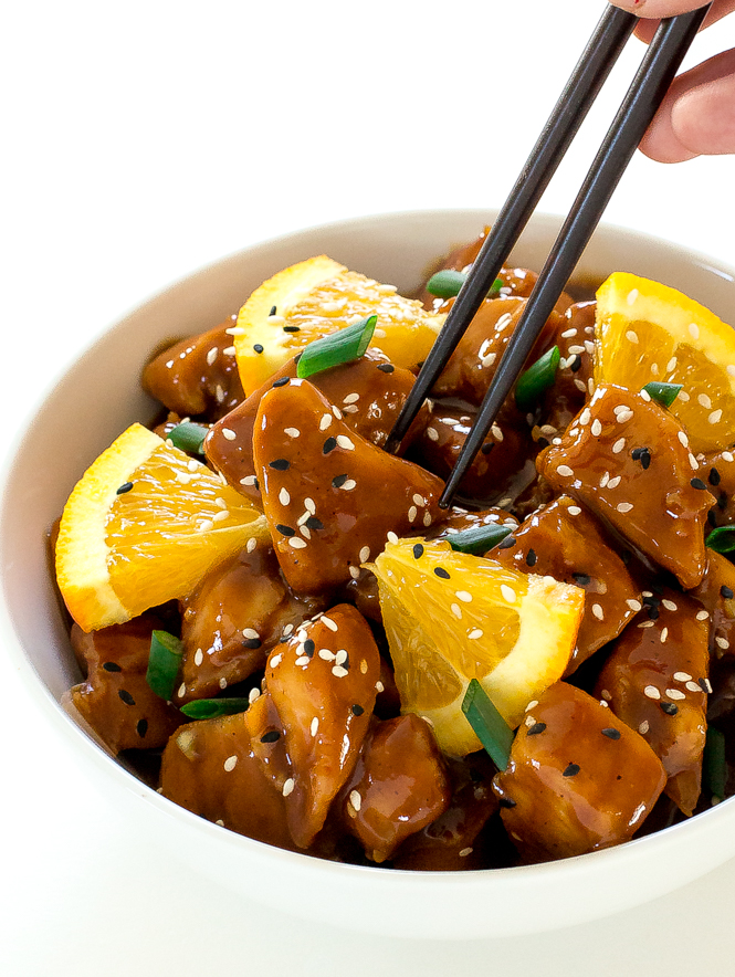 orange chicken in a bowl with orange slices and chopsticks