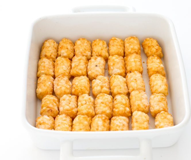 tater tots lined on white baking dish