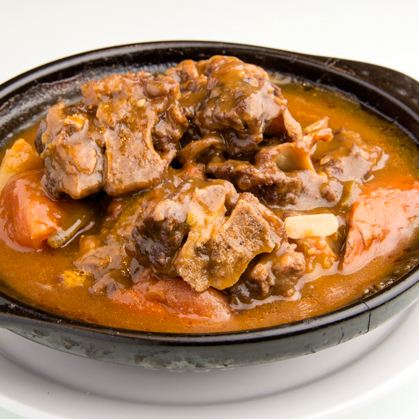 Stewed ox tail with red wine in casserole