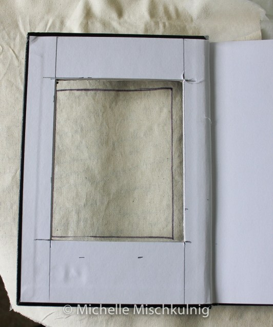 Work out the size of your window and cut through the thick cardboard cover using a staley knife then place the cover over the deli paper/calico. Place it centrally so as edges will fold over to cover the form of the note book trace the window onto the calico.