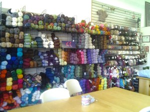 Image of a wall of colorful yarn skeins with a work table in the foreground.