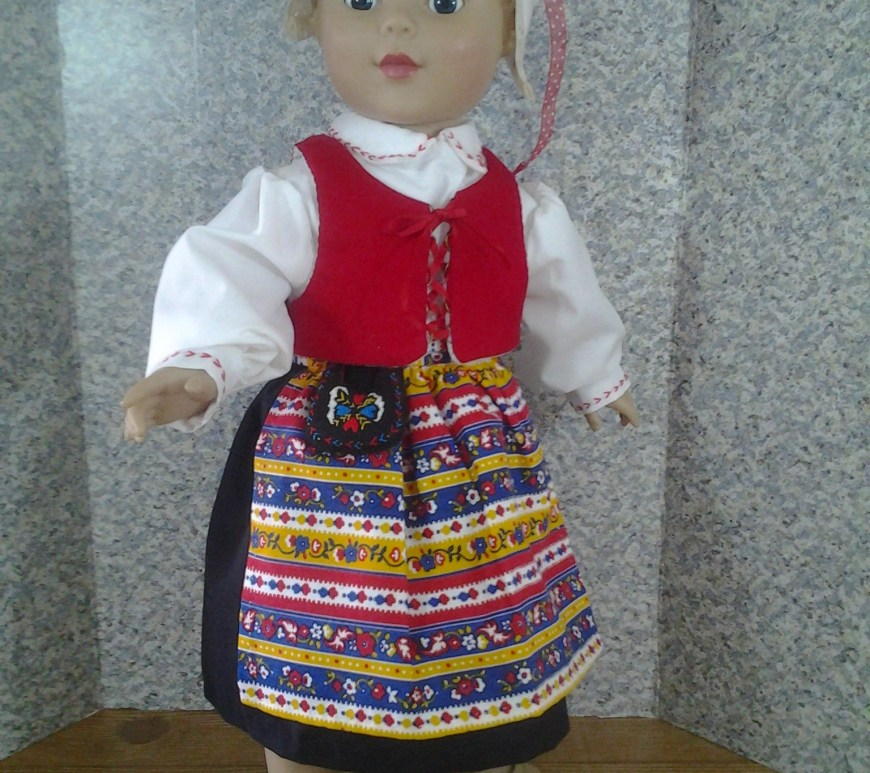 "Here we see an image of an 18 inch Madame Alexander doll wearing a traditional Swedish costume. Around her waist is a felt, hand-embroidered ""pocket,"" a type of purse or bag worn around the waist. The image is watermarked with the website where you can download free printable PDF sewing patterns for making this 18 inch doll outfit, including the pocket, a Pilgrim-style hat or bonnet, a handkerchief, a vest, an apron, a skirt, and a long-sleeved shirt with collar : ChellyWood.com"