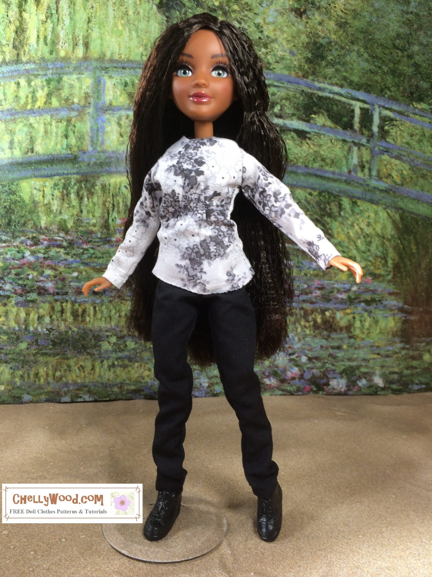 Here we see a Bryden Bandweth doll from the Project MC Squared TV show, modeling a long-sleeved shirt and elastic-waist pants. The shirt is white with a floral print. The pants are black and a bit long on her. She stands in front of a painting of Monet's green bridge with sand at her feet.