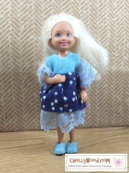 The image shows a Mattel Chelsea doll wearing a handmade doll dress. The dress is made of felt, cotton, and lace. If you would like to make this doll dress for your Chelsea or a similar-sized doll in the 4 inch to six inch size range, please click on the link provided in the caption.