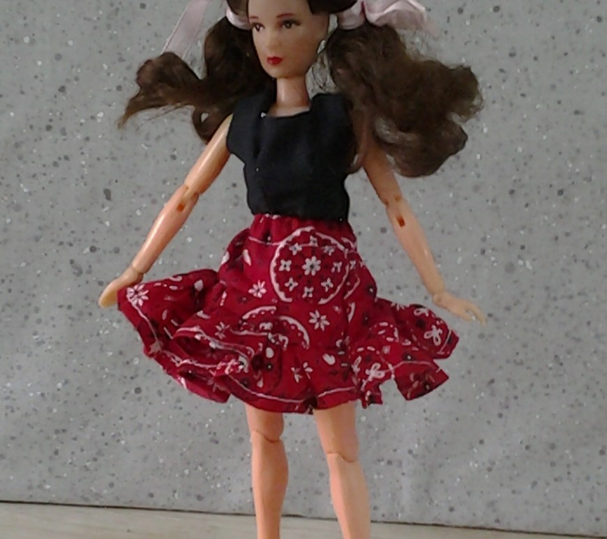 "Image of collectible ""Dorothy"" doll from the Wizard of Oz collection wearing handmade skirt in a western-style print fabric and a solid black crop top."
