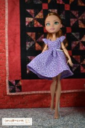 """Click here for all the patterns and tutorials you'll need to make this dress: https: https://wp.me/p1LmCj-GOj The image shows a Ever After High doll wearing a handmade A-line sleeveless dress for tiny-body 8"""" or 9"""" inch dolls like Ever After High dolls. In the diorama where the Ever After High doll stands, there's a tiny tea set on a wicker table, a wicker chair, and a bust of a musical composer resting on a pedestal. The patterns for making this A-line dress for Ever After High dolls are found at ChellyWood.com as a PDF downloadable sewing pattern. Chelly Wood designs free printable sewing patterns for making doll clothes to fit dolls of many shapes and sizes. Go to ChellyWood.com for both the PDF pattern and free tutorial video giving instructions for making this lovely dress which will fit Ever After High dolls and other similar-sized dolls."""
