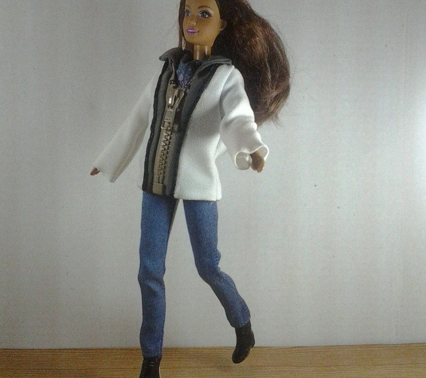 Image of Barbie-sized doll wearing a jacket that zips up the front.