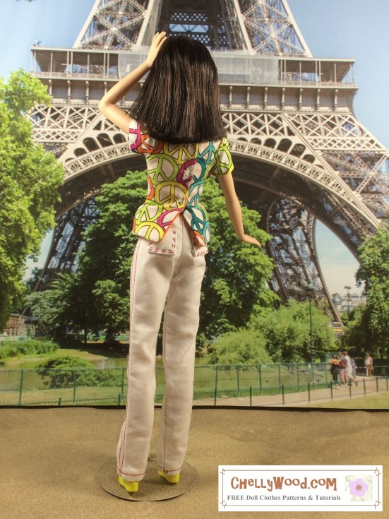"Image of Mattel's ""Tall Barbie"" standing in front of the Eiffel Tower in Paris, wearing a pair of white handmade pants with red seams. Barbie has one hand in her hair and the other at her side. She has her back to us, showing the embroidered pockets of her jeans. She's also wearing a princess-seams shirt decorated with peace signs. Her hair is shoulder-length and a dark chocolate color, and her skin tone is pale. The image includes a watermark that says, ""ChellyWood.com"" for free printable sewing patterns and tutorials."