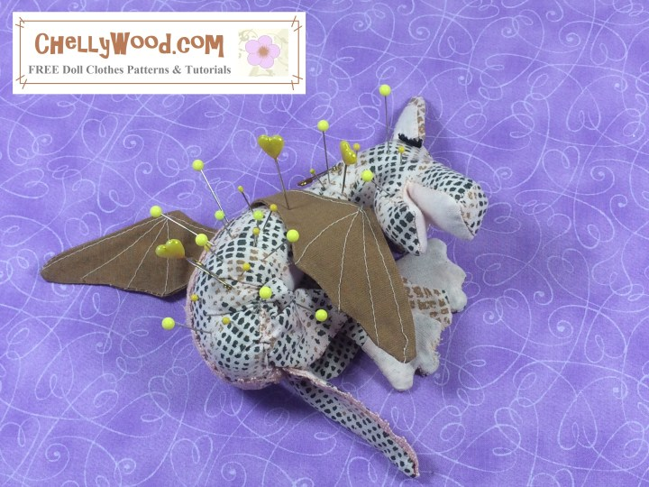 The image shows a baby dragon pincushion curled up into a ball as if he's sleeping. The overlay tells you where you can download the free printable sewing pattern for making this dragon pincushion: ChellyWood.com