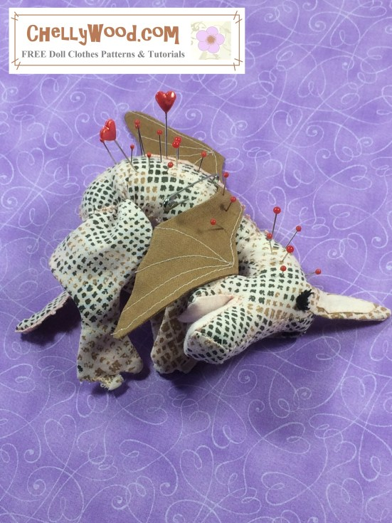 "Image of baby dragon (pin cushion) laying on its belly with sleepy eyes and pins in its back. Overlay says, ""ChellyWood.com: free printable sewing patterns and tutorials"". Background color is purple with a swirly heart pattern."