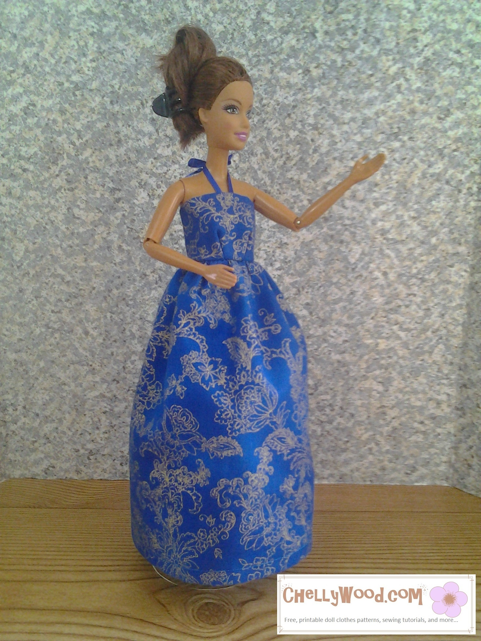 Here we see a Barbie wearing a handmade sun dress with a ribbon that ties around the neck to hold the bodice up. The dress is made of beautiful, vibrant blue fabric with floral embroidery or an embroidery-style print on the fabric. To get to the free pattern for making this dress, please click on the link in the caption.