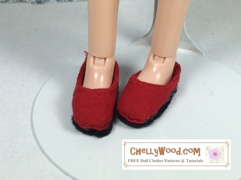 Here we see a pair of doll feet modeling a pair of red shoes. They are slip-on shoes made of red cotton fabric with a tread made of black foam.