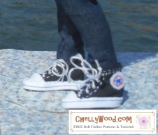 """A doll models a pair of high top sneakers that look a lot like Converse brand high tops. They have the """"all stars"""" look alike logo on them, and they lace up with embroidery floss. The doll stands on a concrete slab near a flowing river. We only see the doll from below the knee, but both sneakers appear in the photo -- right foot and left foot."""