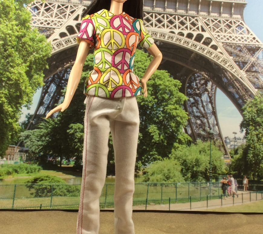 """Image shows Mattels Tall Barbie wearing white jeans and a short sleeved peace sign decorated cotton shirt in front of the Eiffel Tower in Paris, France. Caption reads, """"Chelly Wood dot com for FREE printable sewing patterns to fit dolls of many shapes and sizes."""""""