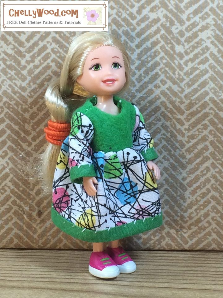 Here we see a tiny 4 inch Kelly doll modeling an Easter dress with long sleeves and a 3/4 length skirt. The sleeves and skirt are trimmed with bias tape. The bodice is made of bright springtime green felt. the skirt and sleeves are made of cotton print fabric that has colorful oval Easter Eggs scattered about with tiny black lines connecting them.