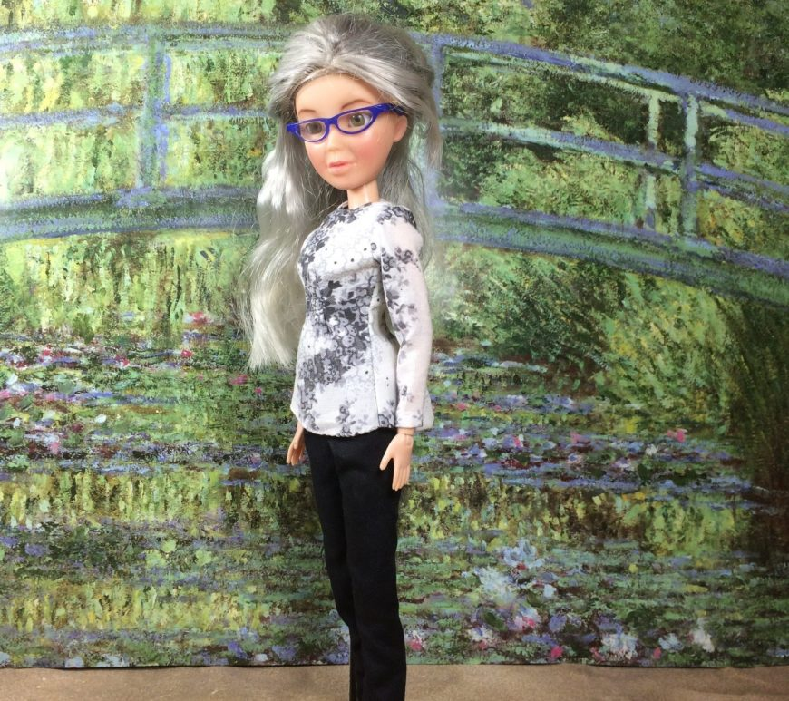 In this photo, the Chelly Wood doll (a re-painted Spin Master Liv doll that wears a grey-haired wig) stands before a huge painting by Monet of the green bridge. She wears a white long-sleeved shirt with flowers swirling across the cotton fabric. She also wears a pair of classic black pants with an elastic waist. The doll wears retro-style cat-eye glasses in with navy blue frames.