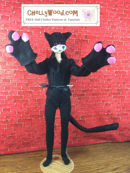 """Image shows a Made-to-Move Barbie® wearing a hand-made cat costume, complete with paw-mittens, tail, felt bodysuit, and felt cat mask. The watermark says """"Chelly Wood dot com FREE printable sewing patterns for dolls of many shapes and sizes."""" The doll stands before a brick background, and her paw-mittens are raised like she's ready to attack. her long cat tail is curved like it's swishing in anticipation of an attack. Her mask has little black whiskers and a tiny pink nose. The ears are pointed but very kitten-like."""