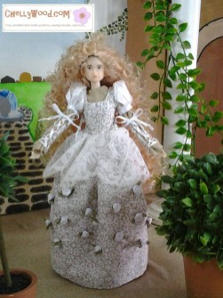 The image shows a Momoko doll with a renaissance gown of lace and ribbons. The skirt of the dress is decorated with tiny white silk roses. Behind her is a garden scene. If you'd like to make this dress, please click on the link in the caption for free printable sewing patterns and tutorial videos.