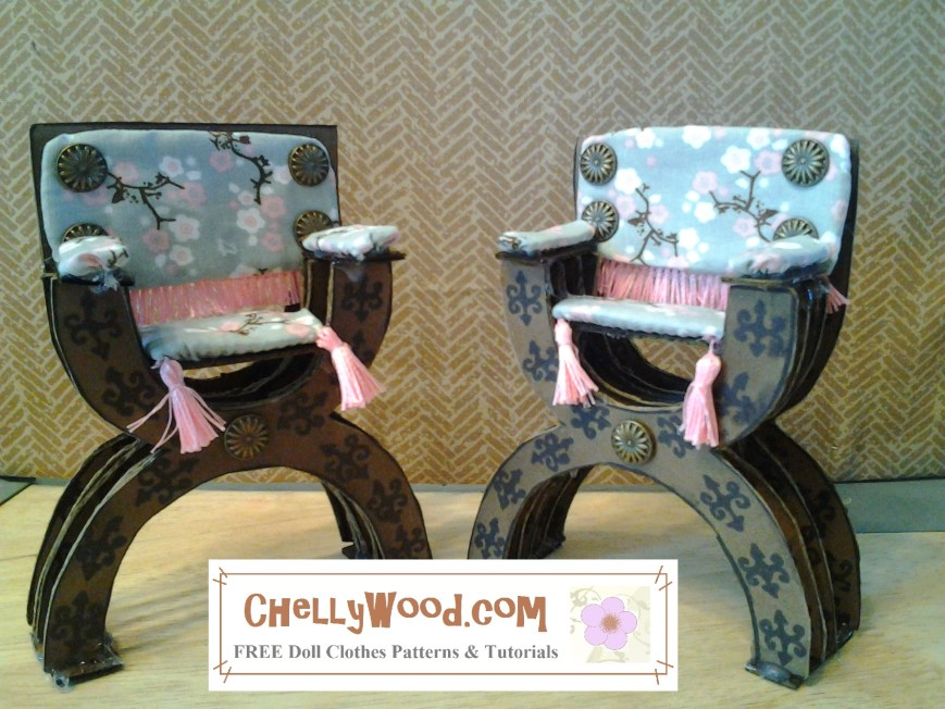 This photo shows two Renaissance style chairs made of cardboard. They have an oriental cotton fabric that creates a plush look to the back, arm rests, and seat of each chair. The seats have tassels hanging down. the back has embroidery floss fringe that hangs from the back to the seat. There are small iron or brass looking buttons on the back of the chair. The legs of the chairs make a sort of X like chromosomes, and they are decorated with fleur de lis patterns in black marker. The legs are layered in a row of four sections to keep the chairs standing upright under the weight of a seated doll (although no doll is shown). The two chairs are elegantly poised at a 45 degree angle to one another.